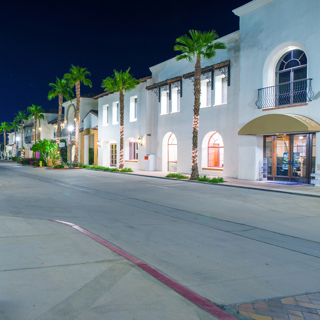 A wide street at night with white buildings and palm trees