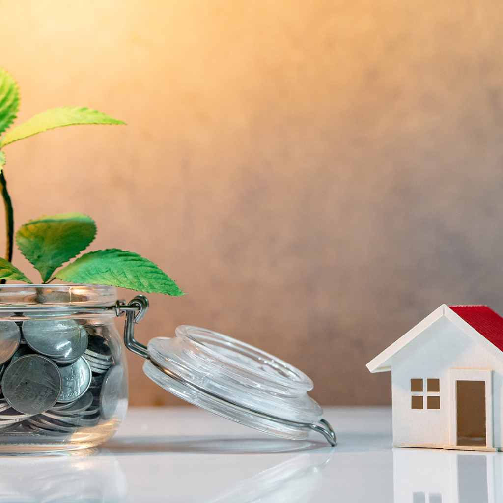 Reflection of green plant growing out of coins in glass jar and house model on the table